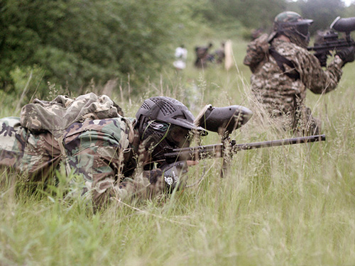 paintball player crawls through grassy terrain